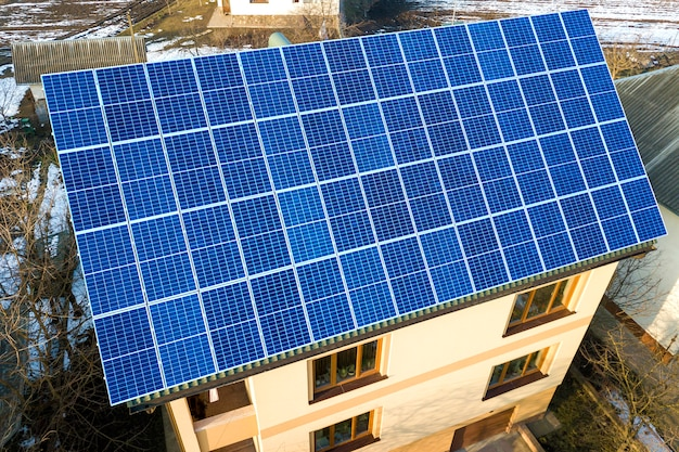 Aerial view of new modern two story house cottage with blue shiny solar photo voltaic panels system on the roof. renewable ecological green energy production concept.