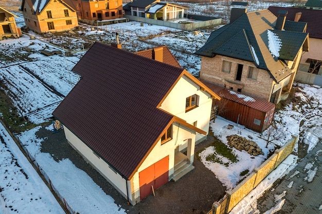 Aerial view of new residential house cottage and attached garage with shingle roof on fenced yard on sunny winter day in modern suburban area.