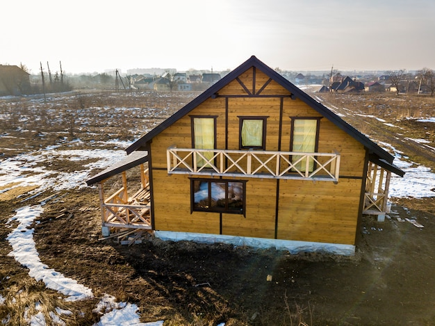 Aerial view of new wooden ecological traditional house cottage of natural lumber materials with steep shingle roof under construction on winter rural landscape background.