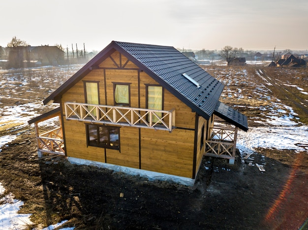 Aerial view of new wooden ecological traditional house cottage of natural lumber materials with steep shingle roof under construction on winter rural landscape