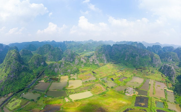 Aerial view of ninh binh region, trang an tourist attraction, scenic river crawling through karst mountain ranges in vietnam, travel destination.