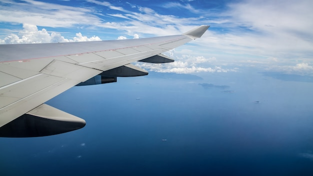 Aerial view of ocean through a plane window. wing of airplane with blue sky and beauty clouds.