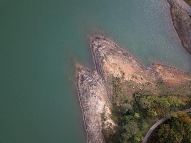 나무 숲과 도로가 있는 댐 은행의 항공 보기