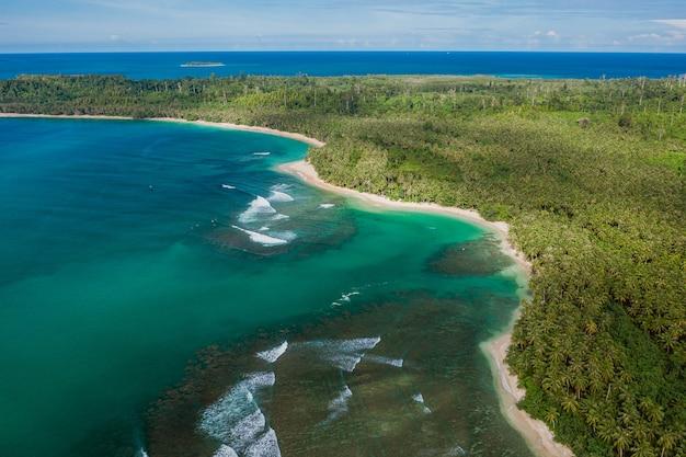 インドネシアの白い砂浜とターコイズブルーの澄んだ水と美しい熱帯のビーチの空撮
