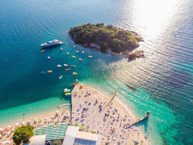 맑은 날에 청록색 물과 편안한 사람들과 아름다운 하얀 모래 해변의 공중보기. 알바니아 크 사밀.
