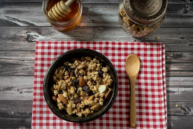 スプーンで木製のテーブルにグラノーラと蜂蜜を添えたボウルの空撮。健康的で自然な食事の概念。
