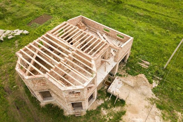 Вид с воздуха на строящийся кирпичный дом с деревянным потолочным каркасом.