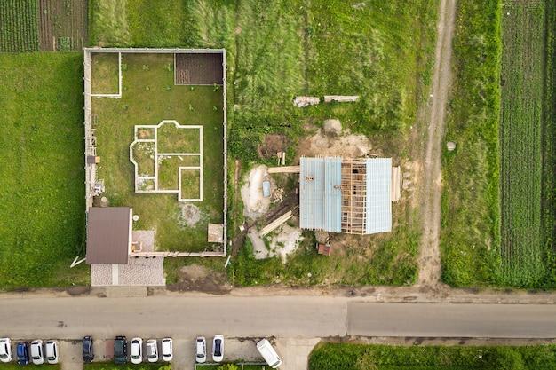 건설 중인 목조 지붕 프레임과 새 프로젝트를 위한 기초가 있는 벽돌집의 공중 전망.