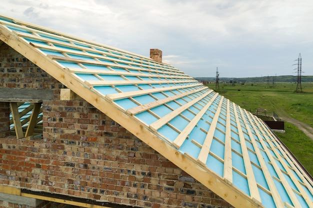 建設中の木製屋根フレームとれんが造りの家の空撮