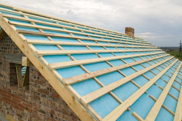 建設中の木製屋根フレームとれんが造りの家の空撮。