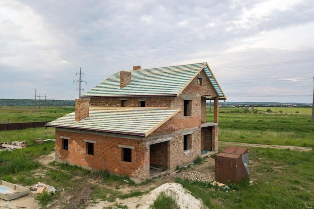 建設中の木製の屋根フレームとれんが造りの家の航空写真。