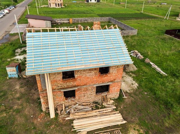 건설 중인 목조 지붕 프레임이 있는 벽돌집의 공중 전망.