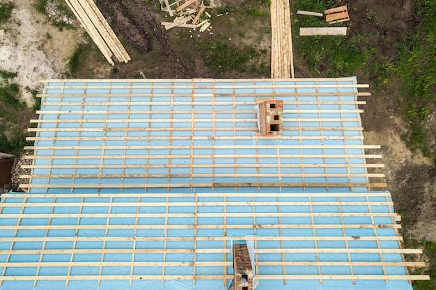 건설 중인 목조 지붕 프레임이 있는 벽돌 집의 공중 전망.