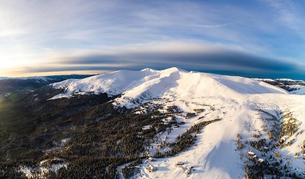 煙のような雲と晴れた凍るような日にモミの木と雪とスキーの丘の中腹の明るく美しいパノラマの空撮。北欧の美しさのコンセプト。