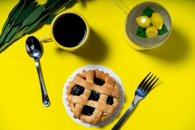 黄色の背景においしいフルーツケーキ、パスタフローラ、自家製クロスタッタのあるカフェの空撮。健康的で自然な食事の概念。横向き。
