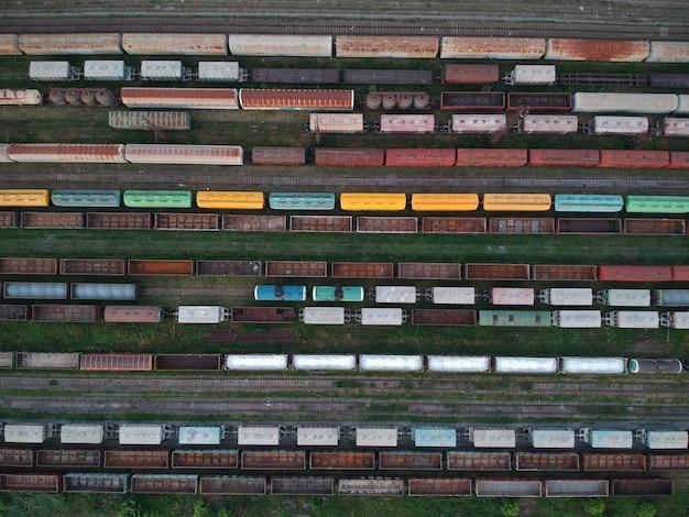 Аэрофотоснимок грузовых поездов. красочные грузовые поезда на железнодорожной станции. тяжелая индустрия.