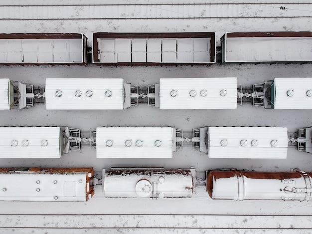 Аэрофотоснимок грузовых поездов в witer. товарные поезда засыпаны снегом на вокзале. тяжелая индустрия. нет людей.