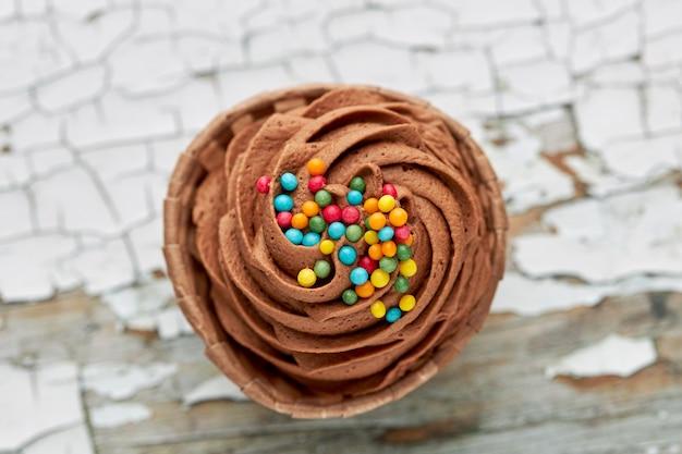 Вид с воздуха на шоколадный кекс с цветными конфетами.