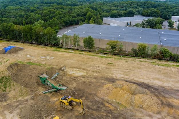 중장비가 있는 건설 현장의 공중 보기는 토지의 등급을 매기고 점토 토양을 옮기고 있습니다.