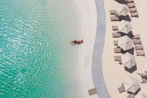 ビーチに一人で横たわって、ターコイズブルーの海の横で夏の太陽を楽しんでいるカップルの空撮