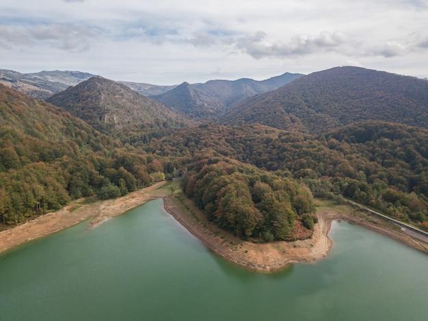 산악 숲 한가운데 흐린 날 일몰에 댐의 공중 전망. 산 강에 댐