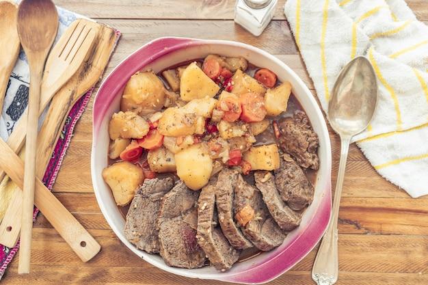 Вид с воздуха на блюдо с домашним тушеным мясом с картофелем и морковью.
