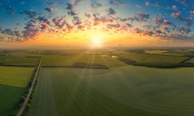 雲と夕日とフィールドの空撮