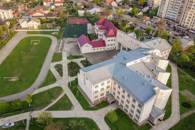 Вид с воздуха футбольного поля на стадионе покрытом зеленой травой и школьным зданием в районе города.