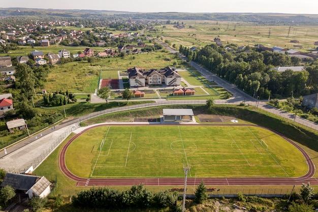 Вид с воздуха на футбольном поле на стадионе покрыты зеленой травой в сельской местности города.
