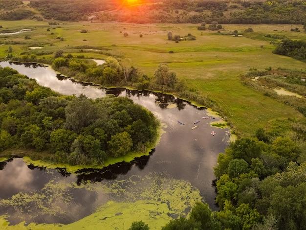夏の日に森の川を旅するカヤックのグループの航空写真