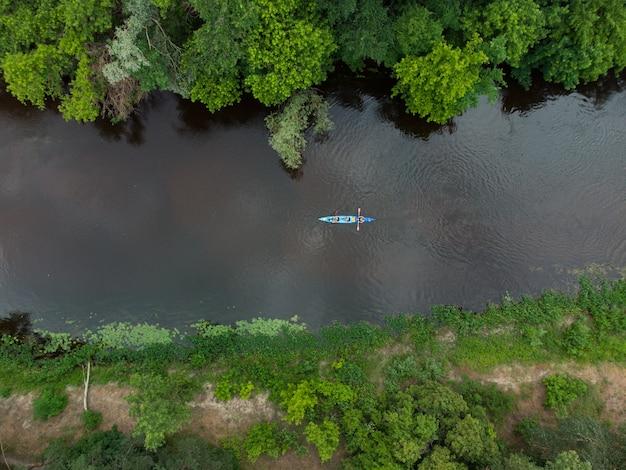 Вид с воздуха на группу каяков, путешествующих по лесной реке в летний день