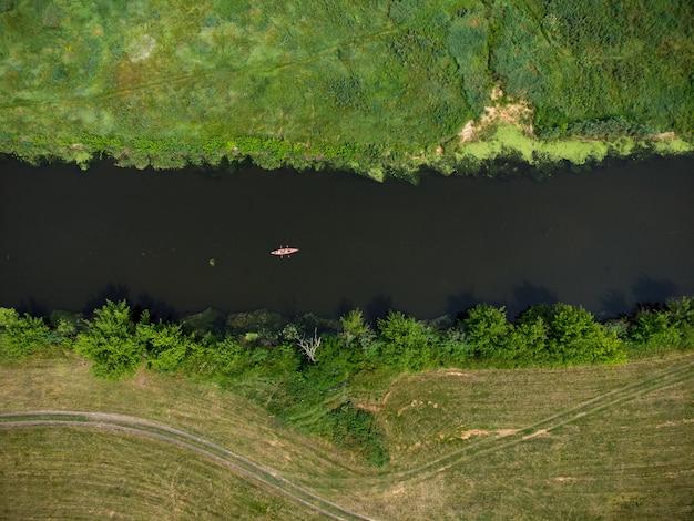 여름날 숲속의 강을 여행하는 카약 그룹의 공중 전망