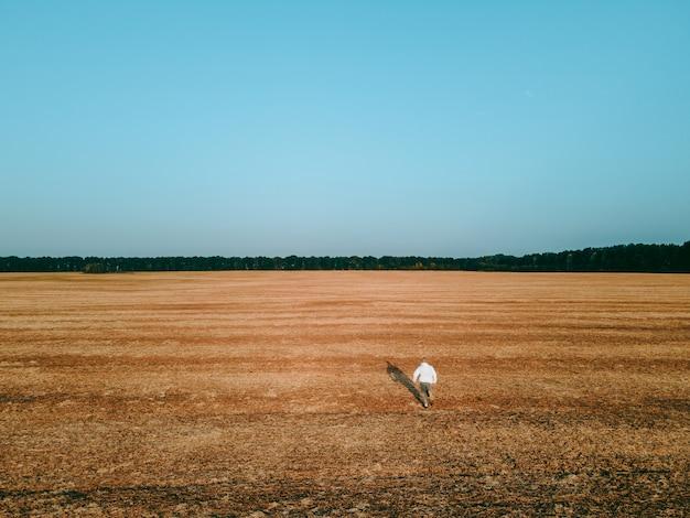 Вид с воздуха на парня, бегущего в поле