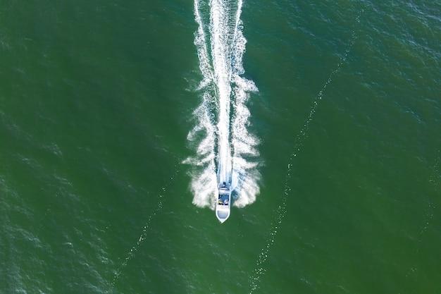 바다를 따라 이동하는 고속 모터 보트의 공중 뷰.