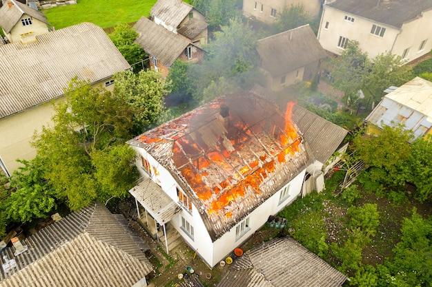 Вид с воздуха на дом в огне с оранжевым пламенем и белым густым дымом.