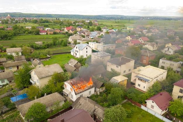 주황색 불길과 하얀 짙은 연기로 불타는 집의 공중 전망.