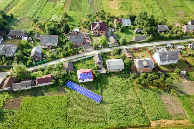 Вид с воздуха дома с голубыми панелями солнечных батарей.
