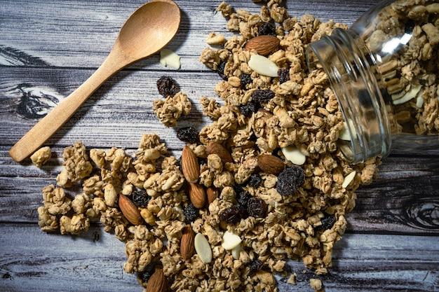 スプーンで木製のテーブルの上にグラノーラをひっくり返した瓶の空撮。健康的で自然な食事の概念。
