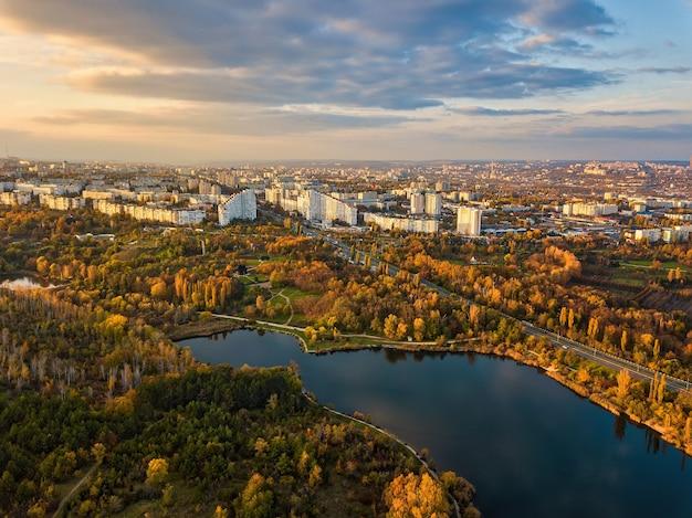 Вид с воздуха на озеро в парке с осенними деревьями. кишинев, молдова. эпический воздушный полет над водой. красочные осенние деревья в дневное время.