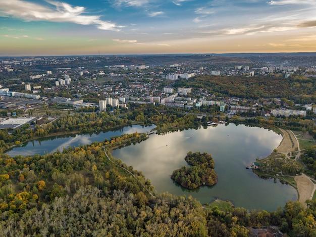 秋の木々のある公園の湖の空撮。