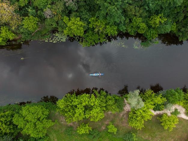 여름날 숲속의 강을 여행하는 많은 카약 그룹의 공중 전망