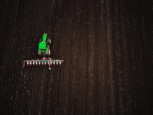 Аэрофотоснимок современного зеленого тракторного посевного сельскохозяйственного поля, подготовка земли к посеву, весна, видео с дрона.