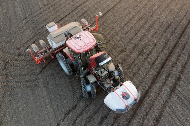 Вид с воздуха на современный многофункциональный трактор, одновременно удобряющий пестицидами, гербицидами и засевающий территорию.