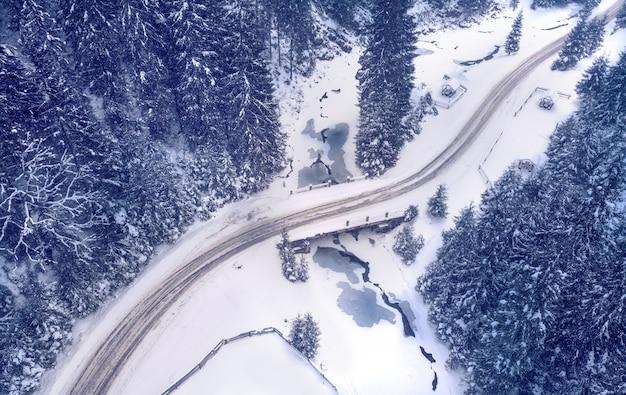 冬の森の山道の空撮。ドロミテアルプスイタリア。