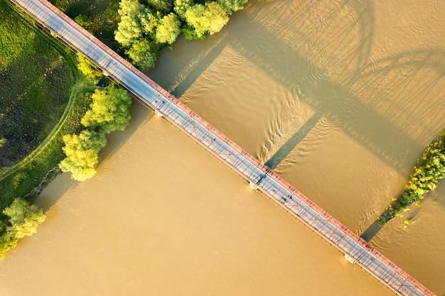 Вид с воздуха на узкий автомобильный мост, протянувшийся через мутную широкую реку в зеленой сельской местности.