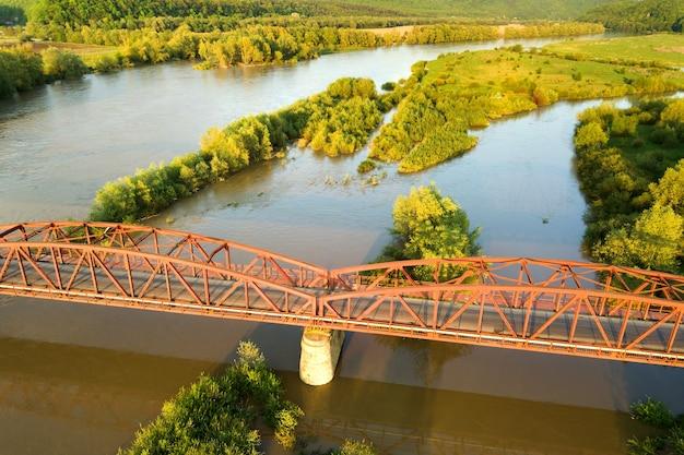 녹색 농촌 지역에서 진흙 투성이 넓은 강 스트레칭 좁은 도로 다리의 공중 전망.