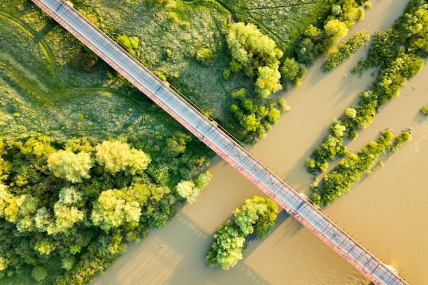 緑豊かな田園地帯の泥だらけの広い川に架かる狭い道路橋の航空写真。