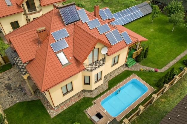 Вид с воздуха на новый автономный дом с солнечными батареями и радиаторами нагрева воды на крыше и зеленом дворе с голубым бассейном.