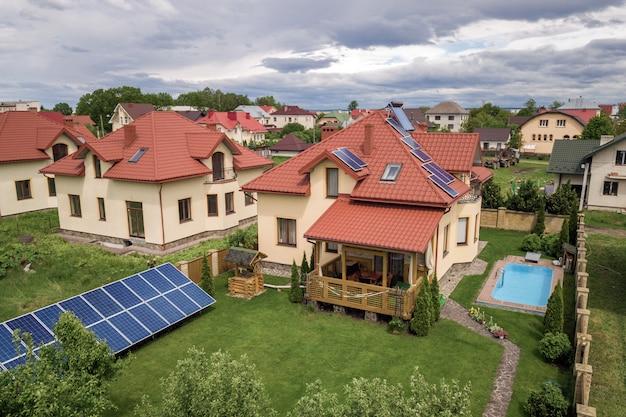 Вид с воздуха на новый автономный дом с солнечными батареями и водяными радиаторами на крыше и зеленым двором с голубым бассейном.