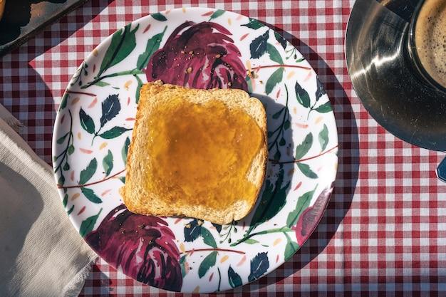 복숭아 잼을 뿌린 토스트가 있는 접시의 공중 전망.